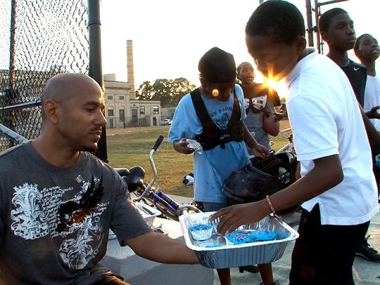 James Famularo hands out cupcakes after Pop Warner
