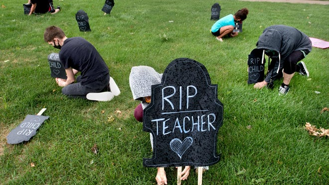 """A group of local activists plant """"tombstones"""" Monday, Aug. 10, 2020 in front of the Peoria Public Schools administration building, 3202 N. Wisconsin Avenue, in protest of the impending coronavirus-affected opening of the district to students and teachers."""