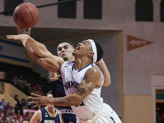 Monmouth guard Justin Robinson (12) is fouled on the