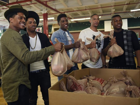 Actors Ephraim Sykes, left, Nathan Davis Jr., Joseph Davis Jones, Peyton Alex Smith and John Boyega display some of the 400 food bags they packed at the Gleaners Food Bank that will be distributed to needy families.