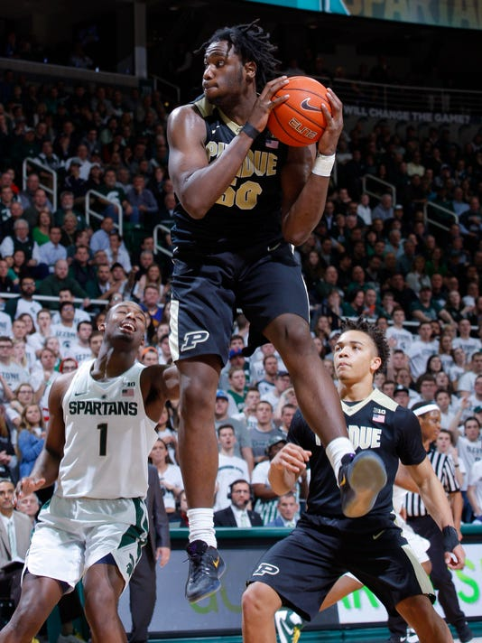 FILE - In this Jan. 24, 2017, file photo, Purdue's Caleb Swanigan, center, pulls down a rebound between Michigan State's Joshua Langford (1) and Purdue's Carsen Edwards during an NCAA college basketball game in East Lansing, Mich. Swanigan ranks as one of the nation's best rebounders and is a frontrunner for Big Ten player of the year. (AP Photo/Al Goldis, File)