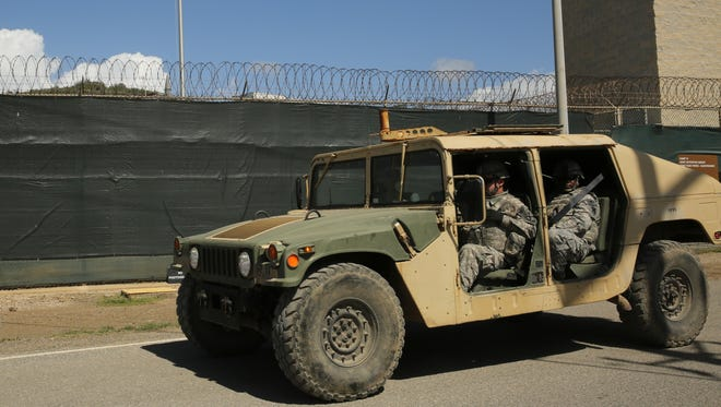 In this Feb. 2, 2016 photo, military personnel patrol outside Camp 6 at Guantanamo Bay, Cuba. After 14 years, the detention center appears to be winding down despite opposition in Congress to President Barack Obama's intent to close the facility and confine the remaining prisoners someplace else.