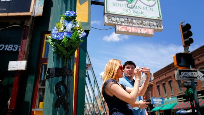 Tourists Jessica Wojciak, left, and Florian Alcade, from Chicago, take photos of Beale Street in Memphis on Sunday, next to one of two memorials at the intersection of B.B. King and Beale near the scene where Memphis Police Department Officer Verdell Smith was struck by a fleeing vehicle and killed. Justine Welch, 21, has been charged with multiple counts including murder and three counts of attempted murder in the crime spree that spread from the Pinch District to south of Beale.