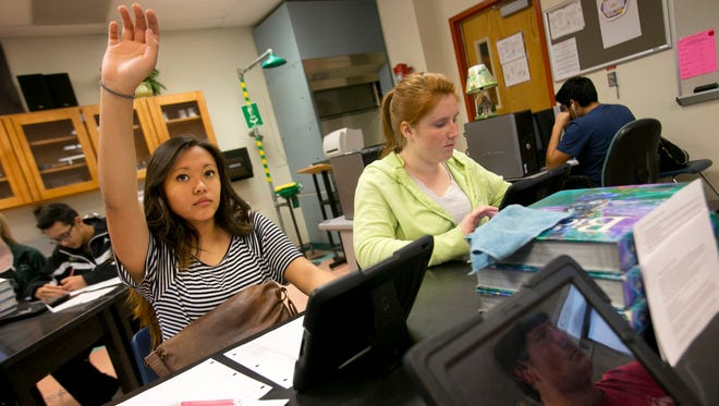 Sophomores (from left) Jamie Chao-Garcia, Tyler Fritz (seen reflected in iPad) and Regina Thoma use information from a virtual lab they completed on an iPad to write a written lab report in a biology class at Skyline High School in Mesa on Thursday, February 6, 2014.