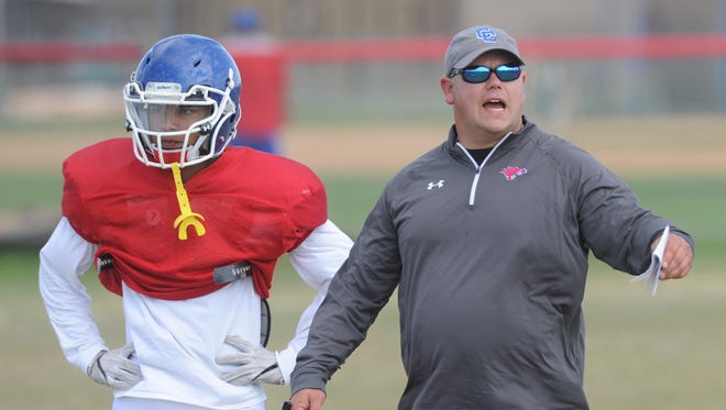 Cooper coach Todd Moebes, right, works with the defense during the Cougars first day of spring practice Monday.