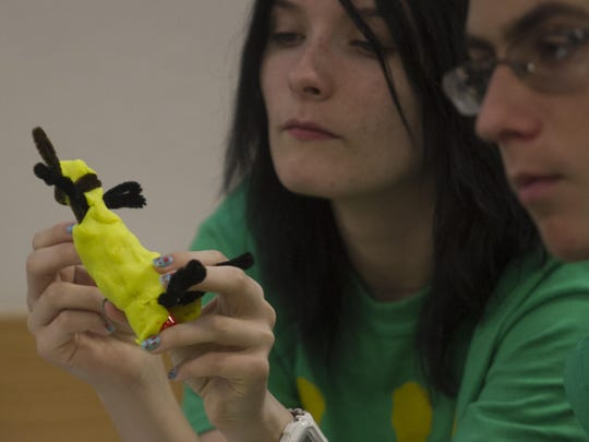 Madison Dryburgh, left, and Ian Milaski work on a figure to demonstrate their product, the SafeLink Scuba Clip, on June 24, 2015, during CEO Academy at FGCU.