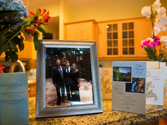 Cards, flowers and a photo of Marc Newberry with his parents, Michele and John, from a recent college event line the kitchen counter of the Newberry home in Naples, Florida on Wednesday, May 3, 2017. Newberry, 20, was killed in a canal boat accident on April 28th.