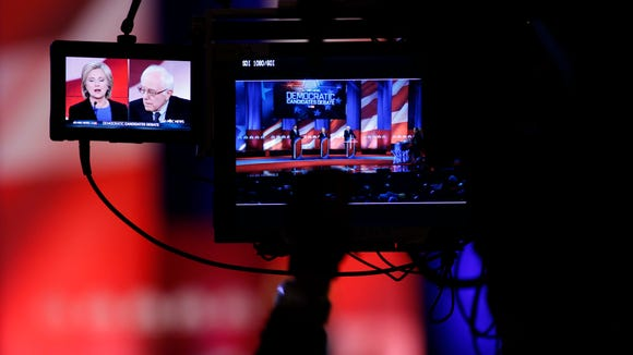A cameraman focuses on Hillary Clinton and Bernie Sanders