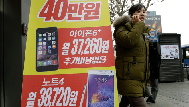 An advertisement poster shows Apple's iPhone 6 Plus, top,  and Samsung Electronics' Galaxy NOTE 4 at a mobile phone shop in Seoul, South Korea, Thursday.