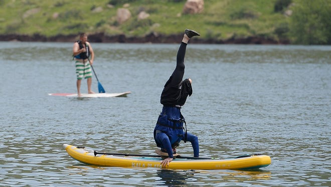 Rustin Hughes does a headstand on a stand up paddle board during Adaptive Watersports Day at Horsetooth Reservoir on Tuesday, June 29, 2016. The annual event, hosted by the City of Fort Collins Recreation Department's Adaptive Recreation Opportunities, provides an opportunity for people with physical disabilities and disabled veterans to go experience the water with the support of adaptive equipment and knowledgeable staff.