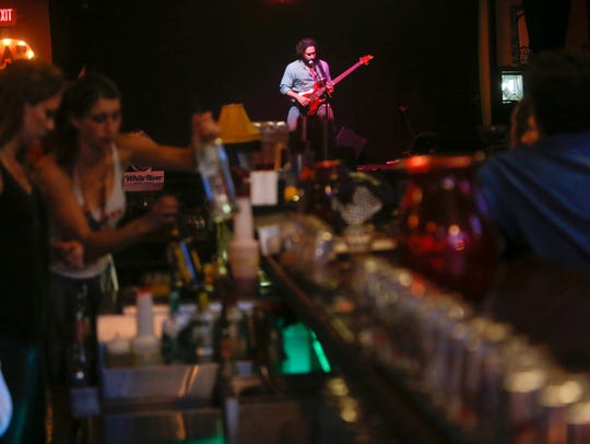 Bar staff work while Shaun Munday performs at Lindberg's Tavern. It is a participant in The Last Straw, a voluntary business effort to reduce or eliminate single-use plastic items.