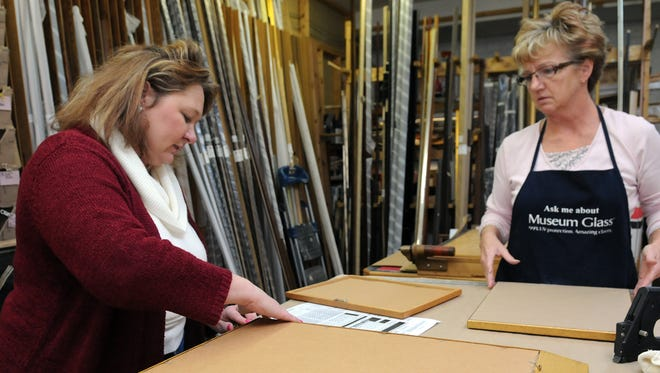 Cindy Smith, left, owner, works with Barb Cottrill on a project Nov. 19 at The Frame Shop in Lancaster.