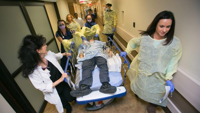 Medical staff members Judie Westbrook (left) and Carrie Gonzalez (right) move Joe Barcala, who pretends to be injured, during a mock trauma call at Chandler Regional Medical Center on March 19, 2014.