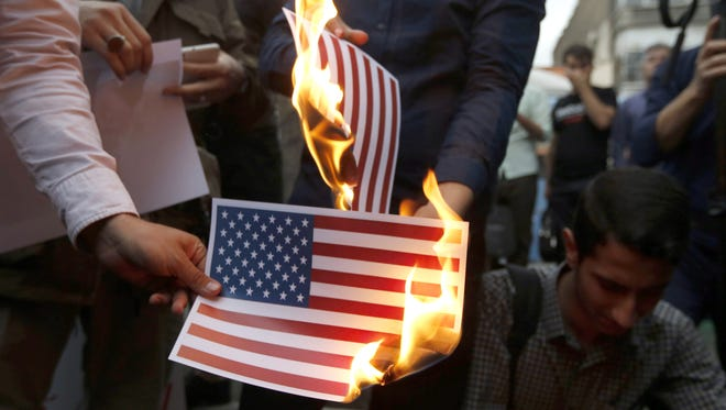 Iranians burning the American flag in Tehran on May 9, 2018.