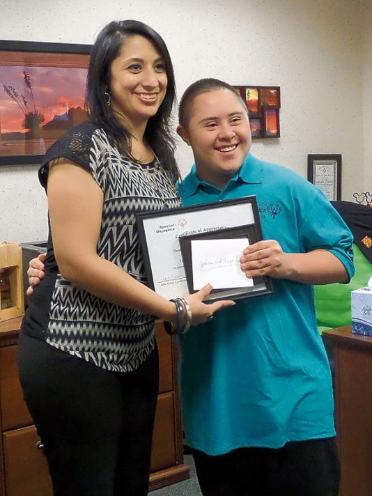 Courtesy Photo   First Financial Credit Union in Deming is sponsoring Arthur Dom Jasso during his bowling season for the Deming Roadrunners Special Olympics team. Jasso will have his bowling fee paid for and also share in the money allowed for travel expenses when the team moves ahead to district and state level competition. Jasso awarded FFCU Branch Director Jessica Garcia with a plaque, portrait and Special Olympics window decal. You can sponsor a Deming Roadrunner by calling Adele Moreno at 575-544-4299 and leave a message.