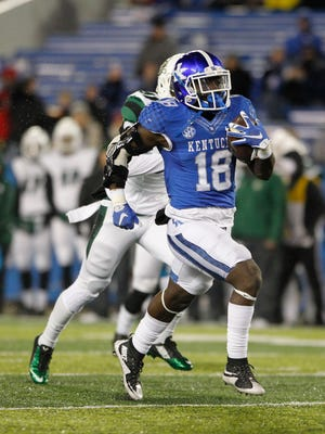 Kentucky Wildcats running back Stanley Boom Williams (18) runs the ball against the Charlotte 49ers in the second half at Commonwealth Stadium.