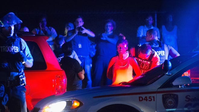A demonstrator is arrested during a protest marking the year anniversary of the death of Michael Brown in Ferguson, Mo., on Aug. 10, 2015.