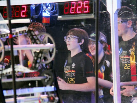 From left, TechFire students Jagr Krtanjek, a York Country Day School eighth-grader, and Adam Wolnikowski, an Eastern York High School 10th-grader, operate and drive the team's robot during a match. The team recently scored high in world competition.