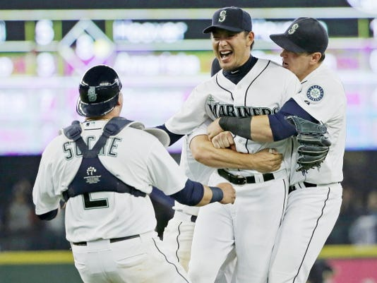 Seattle Mariners starting pitcher Hisashi Iwakuma second from right, celebrates with catcher Jesus Sucre, left, and first baseman Logan Morrison, right, after Iwakuma threw a no-hitter baseball game against the Baltimore Orioles, Wednesday, Aug. 12, 2015, in Seattle. The Mariners beat the Orioles 3-0. (AP Photo/Ted S. Warren)