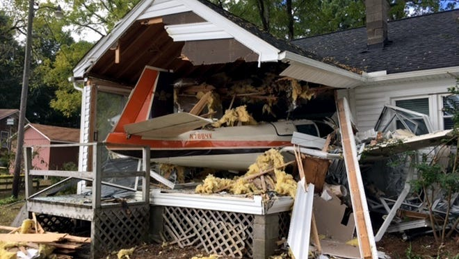 This Saturday, Oct. 7, 2017, photo provided by Virginia State Police shows the wreckage of a small plane after it collided into a house in Middlesex, Va. Officials said the three people on board survived with minor injuries, and no one was home at the time of the crash.