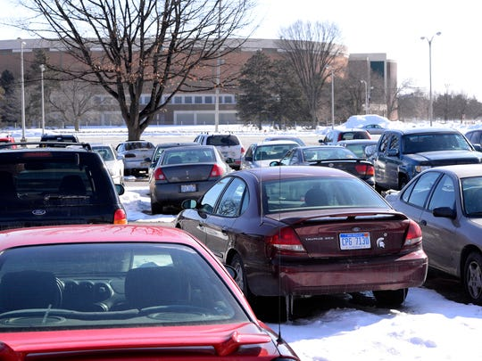Cars in the current parking lot on the possible site of the proposed new $150 million Spartan Village project at Kalamazoo and Harrison streets st MSU Monday 3/2/2015. Proposed plans include a 450,000 square foot apartment complex, an office building for RHS, a community garden anf town homes.