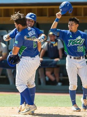 Florida Gulf Coast's Richie Garcia, left, Julio Gonzalez, right meet Nick Rivera at home after a home run during an NCAA baseball tournament regional game against Michigan in Chapel Hill, N.C. on Friday, Jun. 2, 2017.