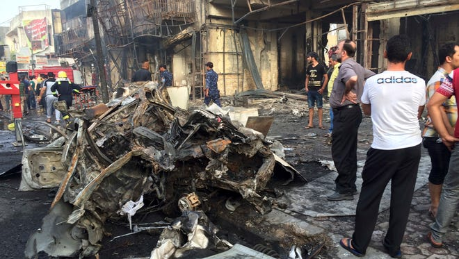 Iraqi security forces and civilians gather after a car bomb hit a crowded area in the Karada neighborhood of Baghdad.