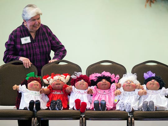 """In this Nov. 21, 2014, photo, Eileen Cancilla, of Belmont, Calif., looks over a selection of Cabbage Patch kids she is considering buying at a collector's convention at Babyland General Hospital, the birthplace of Cabbage Patch Kids, in Cleveland, Ga. """"It's the personality and the look of the baby because we come in here and some draw us to them and some don't,"""" said Cancilla. """"It's the baby that picks us out."""" At home, her and her husband have a collection of about 2,500."""