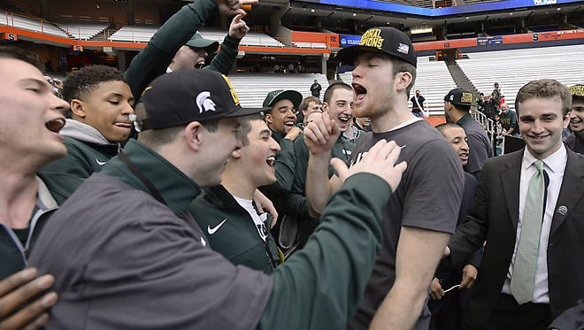 Junior Matt Costello, right, celebrate with MSU's team managers after the Spartans' 76-70 overtime win over Louisville in the NCAA tournament's Elite Eight  on Sunday in Syracuse, N.Y.