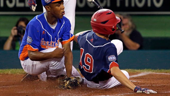 Maine-Endwell's Ryan Harlost scores on a wild pitch by Bowling Green's Devin Obee, left, during the first inning Wednesday at the Little League World Series in South Williamsport, Pennsylvania.