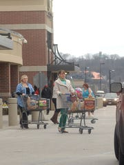 A motorist stops for shoppers as they exit the Kroger