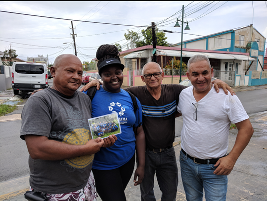 Amena-Devine Ruffin poses for a photo with three Puerto Rico residents including the owner of the second home her group repaired, Jose.