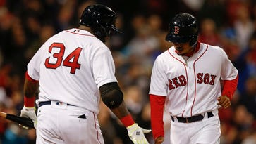 David Ortiz, left, congratulates Red Sox teammate Mookie Betts after scoring a run against the Rockies at Fenway Park.