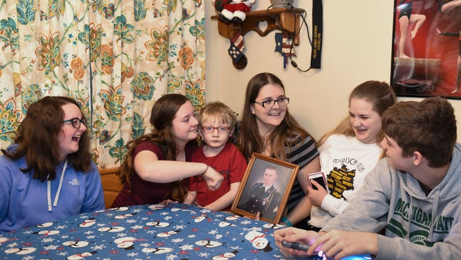 The Rocheleau family from left: Destiny, 16, Liberty, 17, Joshua, 5, Beverly, holding a picture of husband, David, serving in the U.S. Army in South Korea, and twins, Harmony and Gage, 15. A sixth child, who is currently a foster child, is not pictured. They intend to adopt the child.