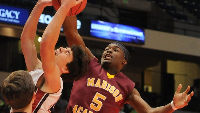 Madison Academy's Joshua Langford blocks a shot by Montgomery Academy's Barton Lester during an AHSAA State Finals Class 3A semifinal basketball game in Birmingham, Ala., Tuesday, Feb. 24, 2015.