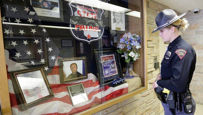 State Trooper Clarissa Justmann looks at a memorial display for Trevor Casper in the State Patrol Headquarters in Fond du Lac. She was on scene when Casper was mortally wounded.