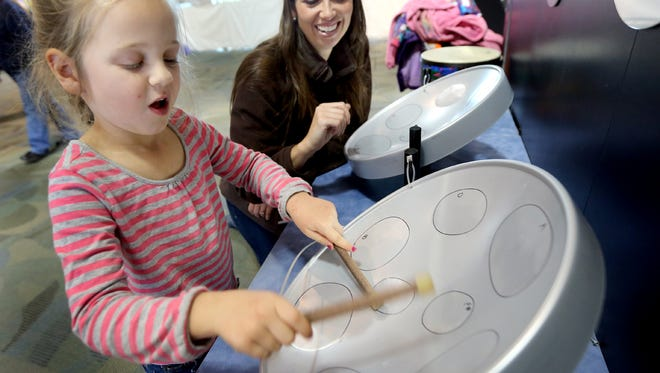 """Lily Stuible plays a tabletop steel drum as her mother, Christina Stuible, a music teacher at Smyrna Elementary, encourages her daughter Saturday during the opening day of """"The Science of Music"""" exhibit at the Discovery Center."""