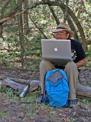 Richard Mahler checks the wild life cameras on his laptop while hiking and observing species in the wilderness.