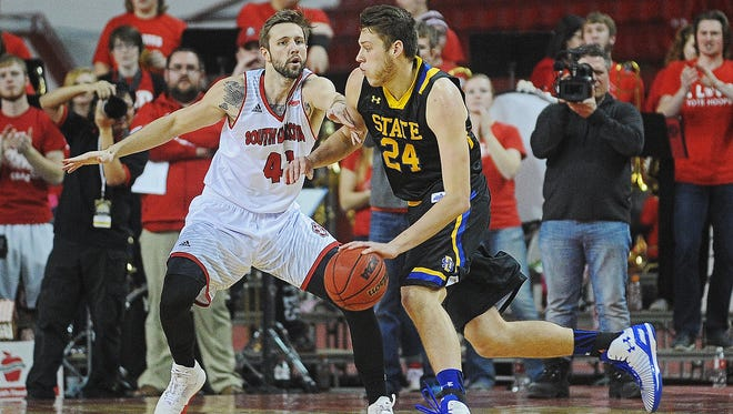 SDSU's Mike Daum (24) drives past USD's Eric Robertson (41) during a South Dakota Showdown Series basketball game Saturday, Jan. 23, 2016, at the DakotaDome in Vermillion, S.D. USD fell 79-75 to SDSU.