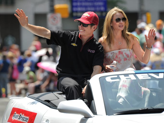 Driver Ryan Briscoe and wife, Nicole, wave to fans as they head north on Meridian Street during the IPL 500 Festival Parade held in downtown Indianapolis on May 26, 2012.