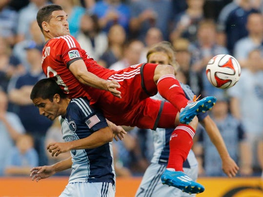 Toronto FC forward Gilberto (9) plays the ball over Sporting Kansas City defender Igor Juliao, bottom, during the first half of an MLS soccer match in Kansas City, Kan., Friday, May 23, 2014. (AP Photo/Orlin Wagner)