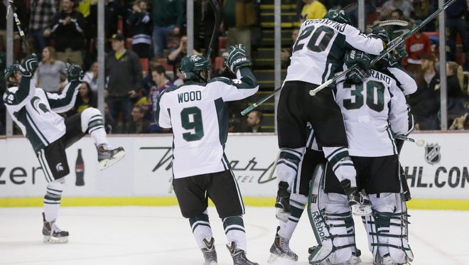 Michigan State hockey players jump on goalie Jake Hildebrand after the team's 2-1 victory over Michigan on Friday, Jan. 30, 2015 at Joe Louis Arena in Detroit.