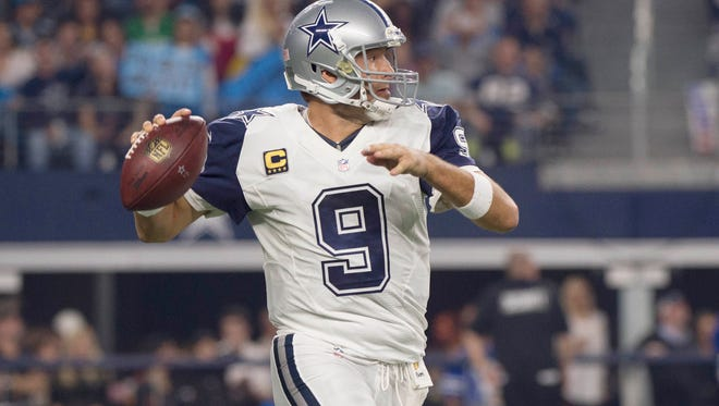 Dallas Cowboys quarterback Tony Romo (9) rolls out to pass against the Carolina Panthers during the first quarter of an NFL game on Thanksgiving at AT&T Stadium.