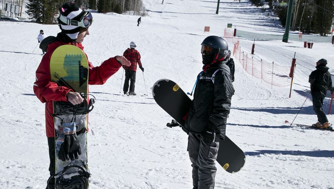 Caitlin Jackson, one of the skiing and snowboarding instructors at Brian Head Resort, talks with her student, Kelton Harris, about his ride down the slope on in this file photo.