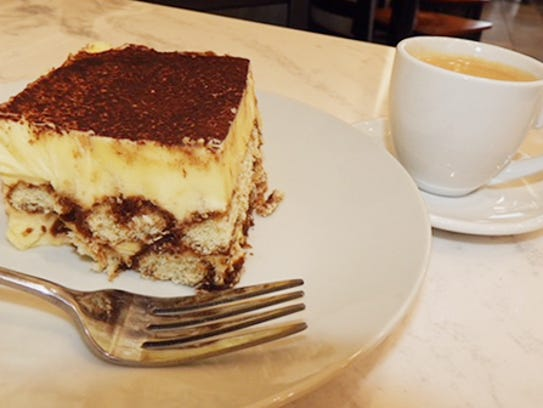 A slice of tiramisu and a double shot of espresso at