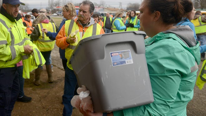 Megan Cook, right, passes out bagged food for volunteers to take into the field with them before they leave from the old Pinson school on Friday in the search for 2-year-old Noah Chamberlin.
