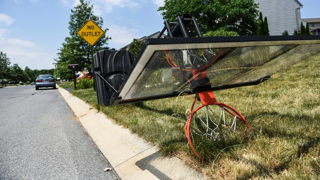 A basketball hoop lies on its side on Wheatland Drive in Wheatland Manor on Tuesday, June 21, 2016. A Jackson Township ordinance states that basketball hoops can't be used in the street.