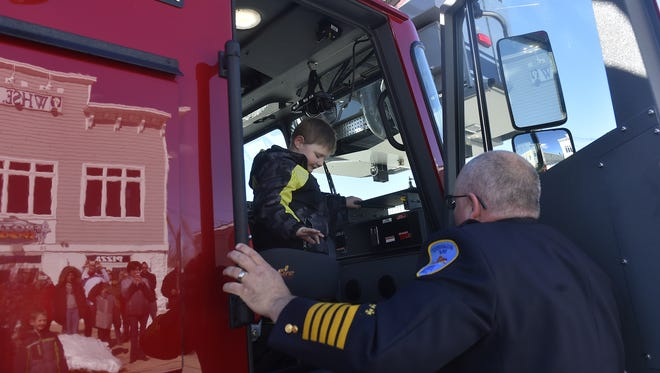 """Sturgeon Bay Fire Chief Tim Dietman helps Chase Hartl, 6, off a fire engine on Saturday afternoon in Sturgeon Bay. The fire department brought the kindergarten student to the Frozen Spoon for a party attended by about 40 friends and family (greeting of his arrival reflected in side of of truck). The """"Delivering the Wish"""" escort and the Wish-Day party was provided by Make-A-Wish."""