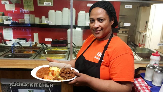 Zeni Meshesha  shows off a plate of the authentic Ethiopian food that she and her husband, Girma Meshesha, serve in their Ajora Kitchen restaurant in The Arcade.