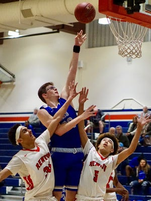 Olympic's Tyler Yost, middle, shoots over Renton's Malik Coats, left, and Jaloni Garner, right, during Tuesday's district playoff game. Yost scored 27 points in the Trojans' 64-55 win.